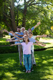 Multi generation family standing in a row with arms outstretched Royalty Free Stock Photography