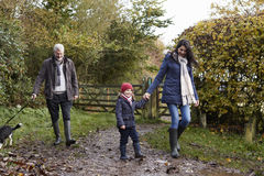 Multi Generation Family Take Dog For Walk In Fall Landscape Stock Photos