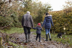 Multi Generation Family Take Dog For Walk In Fall Landscape Stock Photography