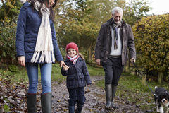 Multi Generation Family Take Dog For Walk In Fall Landscape Stock Photo