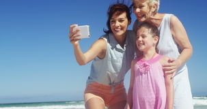 Multi generation family taking selfie from mobile phone at beach stock video