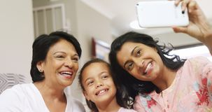 Multi-generation family taking selfie with mobile phone in living room 4k. Multi-generation family taking selfie with mobile phone in living room at home 4k stock video footage