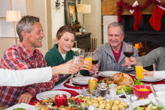 Multi generation family toasting each other at dinner Royalty Free Stock Photos