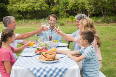 Multi generation family toasting each other at dinner outside Stock Photography