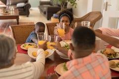 Multi-generation family toasting glasses of orange juice on dining table royalty free stock photo