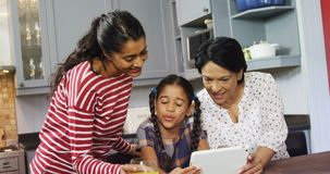 Multi-generation family using digital tablet in kitchen 4k. Multi-generation family using digital tablet in kitchen at home 4k stock video footage