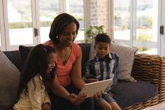Multi-generation family using digital tablet in living room stock images