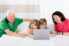 Multi Generation Family Using Laptop At Home Royalty Free Stock Photography