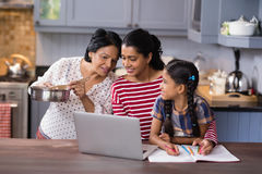 Multi-generation family using laptop in kitchen Royalty Free Stock Images