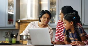 Multi-generation family using laptop in kitchen 4k. Multi-generation family using laptop in kitchen at home 4k stock video footage
