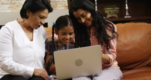 Multi-generation family using laptop in living room 4k. Multi-generation family using laptop in living room at home 4k stock video