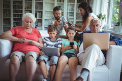 Multi-generation family using laptop, mobile phone and digital tablet Royalty Free Stock Photography
