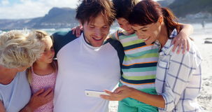 Multi generation family using mobile phone at beach stock video footage