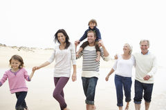 Multi Generation Family Walking Along Beach Together Royalty Free Stock Photography