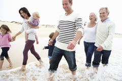 Multi Generation Family Walking Along Beach Together Stock Photo