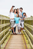 Multi Generation Family Walking On Bridge Taking Photo Royalty Free Stock Image