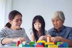 Multi-generation Female members of a family play wooden cubes co. Lur Geeometric ladder together with their grandmother, family time Stock Photography