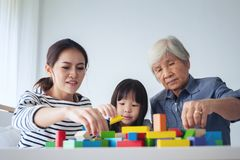 Multi-generation Female members of a family play wooden cubes co. Lur Geeometric ladder together with their grandmother, family time Stock Photo