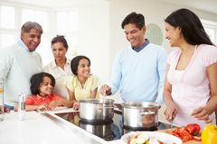 Multi Generation Indian Family Cooking Meal At Home. In Kitchen Talking To Each Other stock image