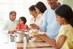 Multi Generation Indian Family Cooking Meal At Home. Serving Food On Plates Royalty Free Stock Photos