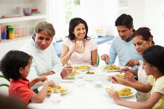 Multi Generation Indian Family Eating Meal At Home. Happy Multi Generation Indian Family Eating Meal At Home In Kitchen Royalty Free Stock Photography