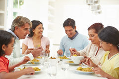 Multi Generation Indian Family Eating Meal At Home. Sitting Down Talking To Each Other Royalty Free Stock Photography