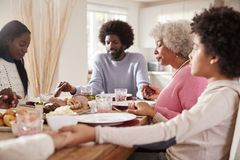 Multi generation mixed race family holding hands and saying grace before eating their Sunday dinner, selective focus royalty free stock photo