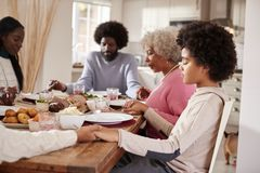 Multi generation mixed race family holding hands and saying grace before eating their Sunday dinner, side view royalty free stock image