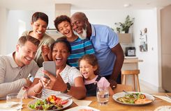 Free Multi-Generation Mixed Race Family Posing For Selfie As They Eat Meal Around Table At Home Together Royalty Free Stock Photos - 166573288