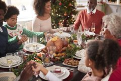 Multi generation mixed race family sitting at Christmas dinner table holding hands and saying grace, elevated view stock photography