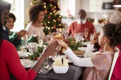 Multi generation mixed race family sitting at Christmas dinner table holding hands and saying grace, selective focus, close up stock images