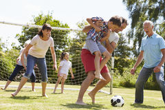 Multi Generation Playing Football In Garden Together Stock Photo