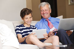 Multi generation shopping online. Portrait of grandfather with laptop and his grandson with digital tablet sitting at home and using credit card for online Stock Images