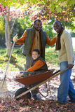 Multi-generational family doing yard work in autumn Royalty Free Stock Photography