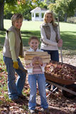 Multi-generational family doing yard work in autumn Stock Photo