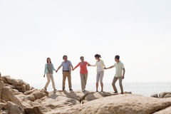 Multi-generational family holding hands on rocks by the sea Royalty Free Stock Image