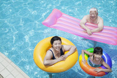 Multi-generational family playing in the pool with inflatable tubes, looking at camera stock photography