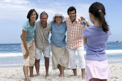 Multi-generational family standing on beach, girl (6-8) filming with camcorder, smiling stock images