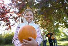 Multi-generational family standing in garden in autumn, focus on girl (6-8) holding pumpkin, smiling, portrait Stock Photography