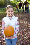 Multi-generational family standing in garden in autumn, focus on girl (6-8) holding pumpkin, smiling, portrait Stock Images