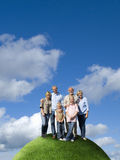 Multi-generational family on top of grassy globe Royalty Free Stock Images