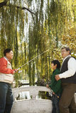Multi-generational men fishing at lake Royalty Free Stock Photography