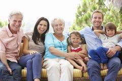 Multi Generations-Familie, die auf Garten Seat sitzt Lizenzfreies Stockfoto