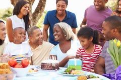 Multi Generations-Familie, die Geburtstag im Garten feiert lizenzfreies stockbild