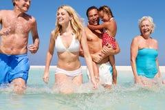 Multi Generations-Familie, die Spaß im Meer am Strand-Feiertag hat Stockbild