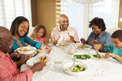 Multi Generations-Familie, die zu Hause Mahlzeit genießt Stockfotos