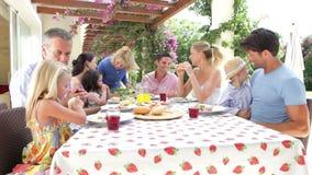 Multi Generations-Familie, die zusammen Mahlzeit im Freien genießt stock footage