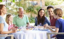 Multi Generations-Familie, die zusammen Mahlzeit im Freien genießt lizenzfreies stockbild