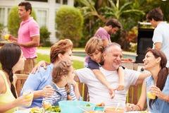 Multi Generations-Familie, die zusammen Mahlzeit im Garten genießt lizenzfreie stockfotos