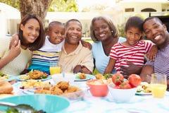 Multi Generations-Familie, die zusammen Mahlzeit im Garten genießt lizenzfreies stockfoto